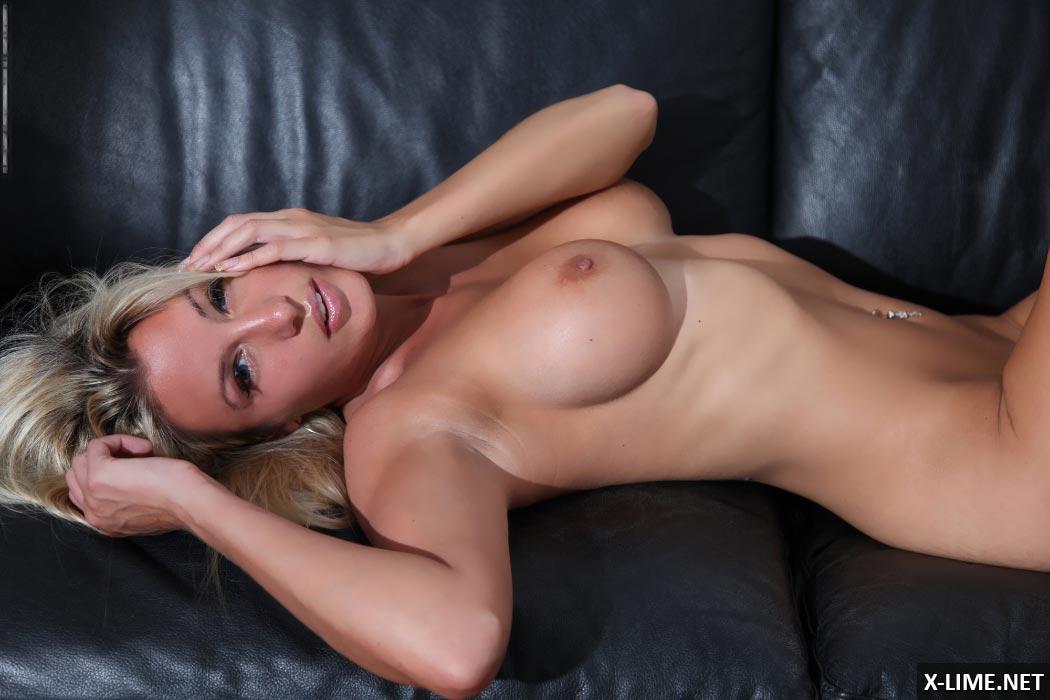 Пышногрудая блондинка на кожаном диване