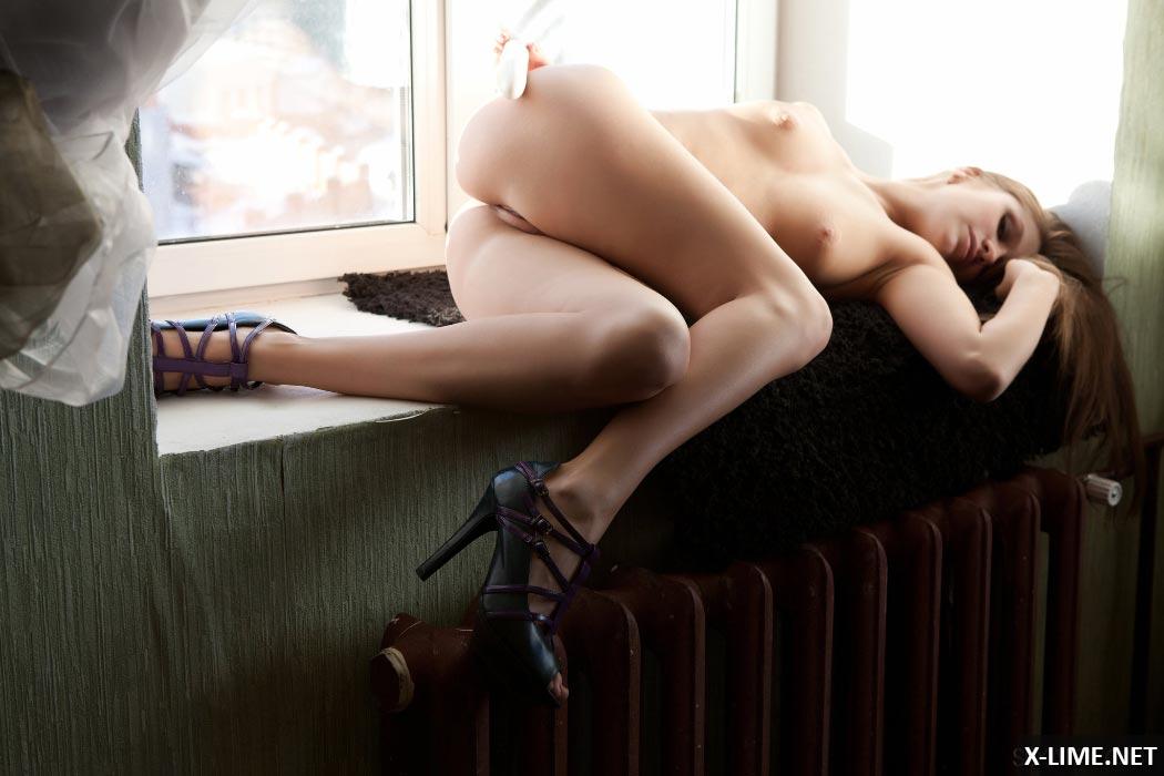 Красивая девушка мастурбирует у окна