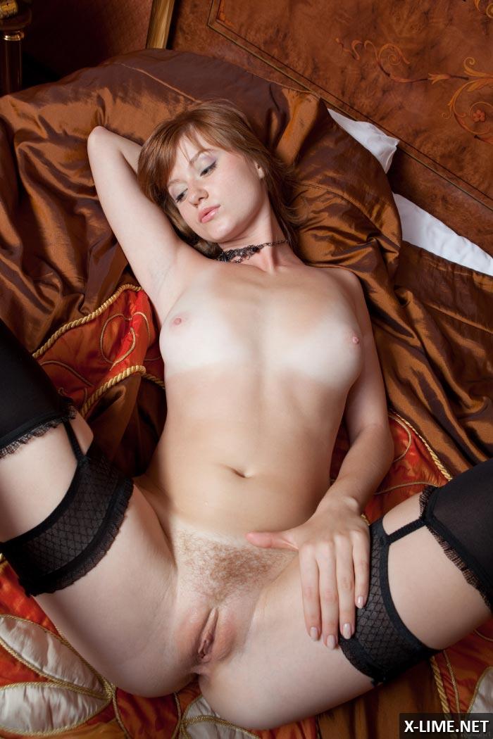 Обнаженная рыжая девушка позирует на кровати